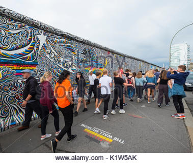 Viele Touristen vorbei Wandbild auf ursprüngliche Abschnitt der Berliner Mauer an der East Side Gallery in Berlin gemalt, Deutschland Stockbild