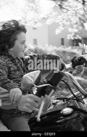 Junge auf dem Motorrad mit Papa Stockbild