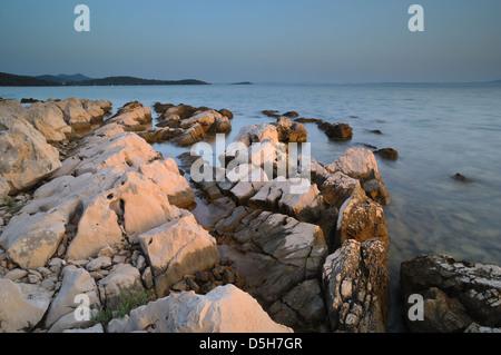 Kroatien/Kornati / otok Hvar - Farben des Sonnenuntergangs am steinigen Strand von Kornati National Park suchen Stockbild