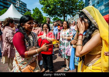 """Eine Frau trägt einen Sari bringt Segen mit Feuer während der Zeremonie. Das Festival der Wagen, auch bekannt als Ratha Yatra, ist ein zeitloses Festival, mit Ursprung in der antiken Stadt Jagannatha Puri in Indien. Seit Tausenden von Jahren, haben zu Jagannatha Puri wurde in Indien in das älteste Festival der Welt namens Ratha-yatra"""", den Wagen Festival"""". Jetzt Ratha-yatra wird jedes Jahr in Dutzenden von Städten rund um die Welt abgehalten. Das ratha Yatra Festival hat einen gemeinsamen Blick in den meisten großen Städten der Welt werden seit 1968 durch die ISKCON, Hare Krishna Bewegung. In Rot Stockbild"""