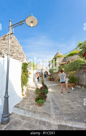 Alberobello, Apulien, Italien - 1. JUNI 2017 - Touristen zu Fuß, eine traditionelle Straße in Alberobello Stockbild
