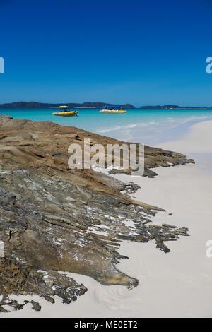 Felsformationen und weißen Sand am Whitehaven Beach mit verankerten Boote entlang der Whitsunday Islands in Queensland, Australien Stockbild