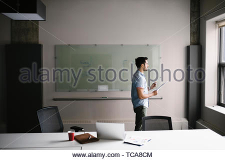 Nachdenklich Geschäftsmann Bürofenster mit Blick Stockbild