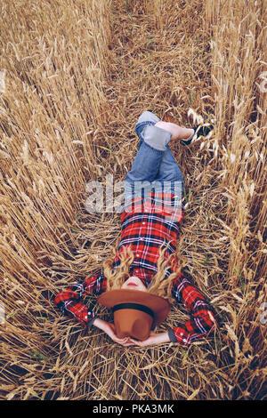 Junge Frau mit Stil liegt in einem Feld von Weizen Stockbild