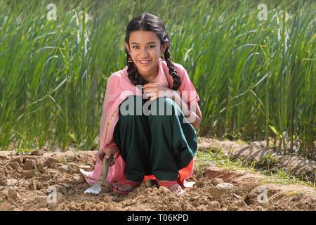 Glückliche kleine ländliche Mädchen graben Bodens mit Hilfe einer Kelle sitzen in der Landwirtschaft. Stockbild