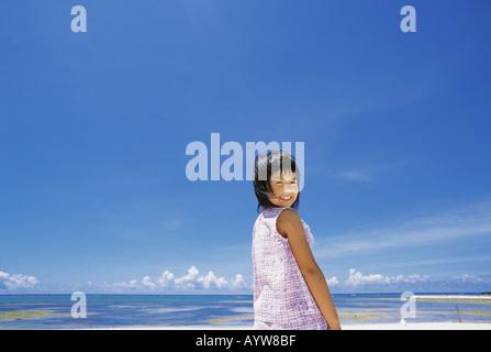Mädchen im Rückblick und lächelnd am Strand Stockbild