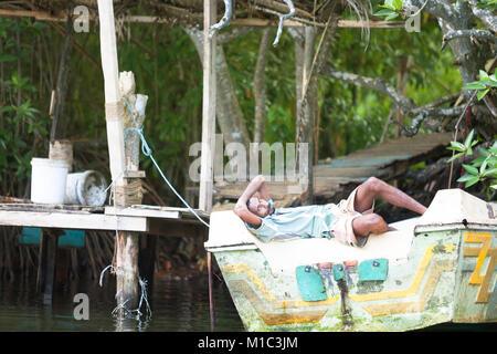 Madu Ganga, Balapitiya, Sri Lanka - Dezember 2015 - Ein Fischer seine Siesta auf einem Motorboot, Asien Stockbild