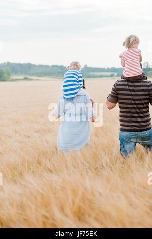 Familie mit zwei Kindern, die zu Fuß in Feld Stockbild