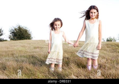 Schwestern in Kleidern im Feld stehen Stockbild