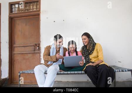 Happy Village Mädchen sitzen mit ihren Eltern auf einem Feldbett, die ein Laptop. Stockbild