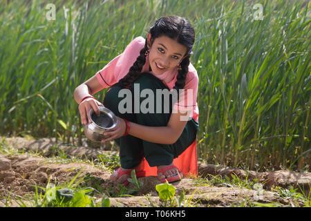 Gerne kleine Mädchen sitzen kleine Pflanzen Bewässerung in der Landwirtschaft. Stockbild