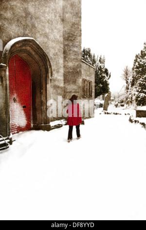 Frau zu Fuß durch den Schnee auf einem Friedhof Stockbild