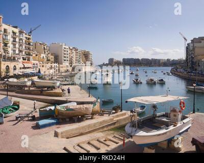 Spinola Bay in St. Julian's Malta eine geschützte Bucht mit Fischerbooten, Verkehr, Restaurants und Unterkünfte für Touristen Stockbild
