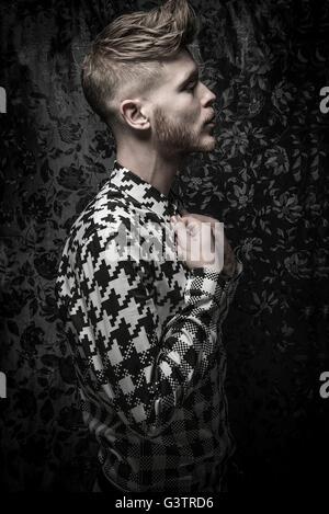 Studio-Porträt eines bärtigen jungen Mannes in einem schwarzen und weißen Hemd. Stockbild