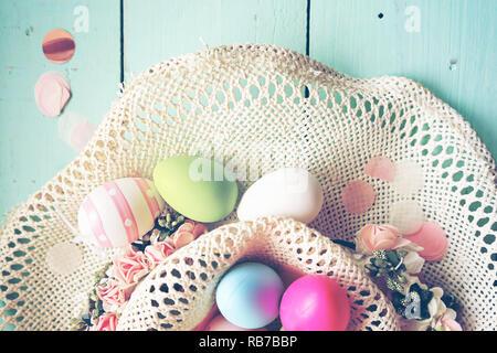 Ein wunderschönes und farbenfrohes Close-up Flachbild der Ostereier in Pastelltönen und in einem Korb mit Blumen und Streifen Stockbild