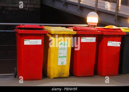 Bunte Mülltonnen, gelbe Tonne für plastik Müll, rote Tonne für Glas Müll in der Dämmerung, Bremen, Deutschland, Europa ich Bunte Mülltonnen, Gelbe Tonne f Stockbild