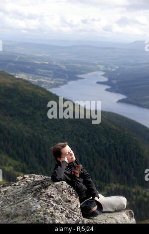Frau sitzt auf einer Klippe Stockbild