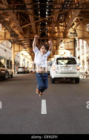 Junge, springen auf der Straße Stockbild