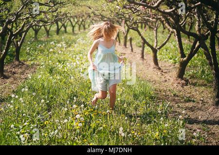Lächelnde Frau läuft unter den Blumen. Frieden und Harmonie Stockbild