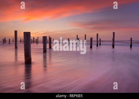 Holzpfähle, die in der Brandung am Strand. Bei Sonnenuntergang fotografiert. Stockbild