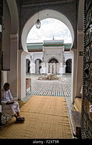 Mann liest den Koran in den Eingang der Kairaouine-Moschee in Fes, Marokko Stockbild