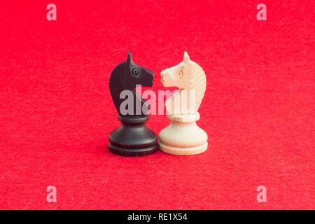 Weißes Pferd und schwarzes Pferd, traditionell in Schach Spiel konfrontiert, haben abgestimmt. Bild in isolierten roten Hintergrund. Stockbild