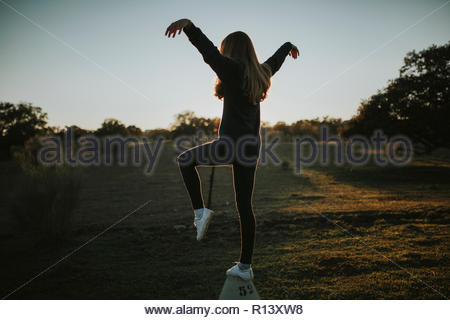 Volle Länge Schoß einer Frau posiert in einem Feld bei Sonnenuntergang Stockbild