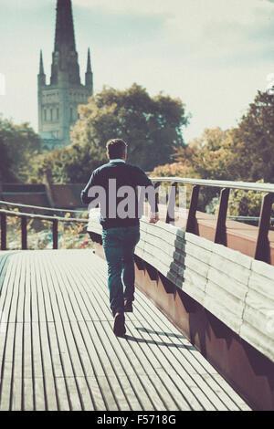 Mann läuft über städtische Brücke mit Kirche im Hintergrund Stockbild