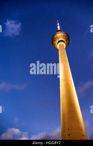 Berlin, Mitte.Alexanderplatz. Beleuchtete goldene Fernsehturm (Fernsehturm) vor dramatischen Abendhimmel Stockbild