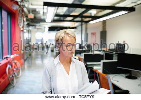 Geschäftsfrau Wandern und Lesen Schreibarbeiten im Büro Stockbild