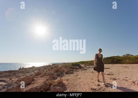 Cap de Ses Salines, Mallorca, Spanien - eine junge Frau, die sich für einen Spaziergang am Strand von Ses Salines Stockbild