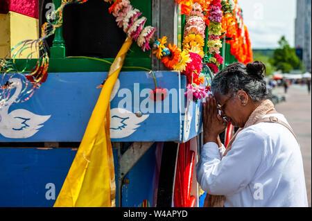 """Eine indische Frau betet im Heiligen Wagen während der Feier. Das Festival der Wagen, auch bekannt als Ratha Yatra, ist ein zeitloses Festival, mit Ursprung in der antiken Stadt Jagannatha Puri in Indien. Seit Tausenden von Jahren, haben zu Jagannatha Puri wurde in Indien in das älteste Festival der Welt namens Ratha-yatra"""", den Wagen Festival"""". Jetzt Ratha-yatra wird jedes Jahr in Dutzenden von Städten rund um die Welt abgehalten. Das ratha Yatra Festival hat einen gemeinsamen Blick in den meisten großen Städten der Welt werden seit 1968 durch die ISKCON, Hare Krishna Bewegung. In Rott Stockbild"""