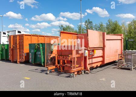 Orange abfallpressen stehen auf einem Fabrikgelände mit anderen Abfallbehälter neben Ihnen Stockbild