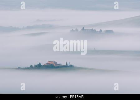 Am frühen Morgen Nebel verweilenden Unter den Villen und Bauernhäuser im Val d'Orcia, UNESCO-Weltkulturerbe, Toskana, Italien, Europa Stockbild