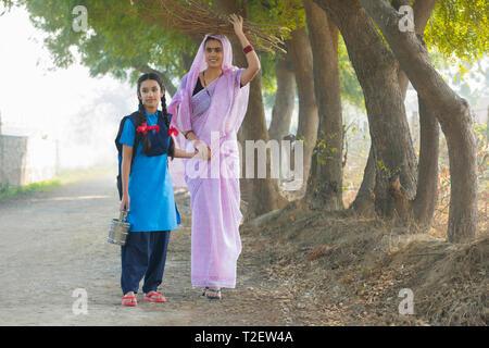 Ländliche Frau Brennholz tragen auf dem Kopf gehen mit ihrer Schule Tochter im Dorf. Stockbild
