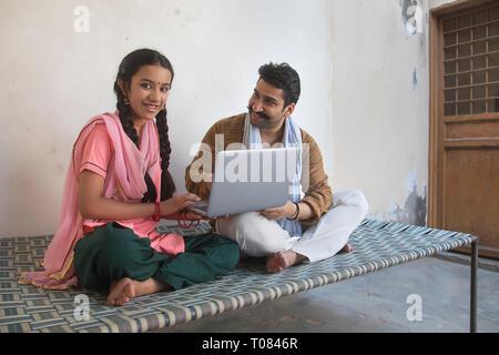 Happy Village Mädchen sitzen mit ihrem Vater auf einem Feldbett mit Laptop Computer. Stockbild