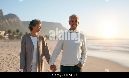 Im Freien Schuss glücklich älteres paar spazieren am Strand. Senior Mann und ältere Frau bei einem Stockbild