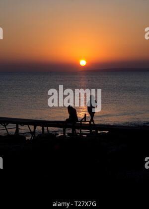 Sonnenuntergang in Ayia Napa Zypern, einem bunten sunn Einstellung im Mittelmeer mit Silhouettiert Touristen Stockbild