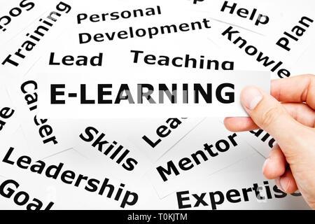 Hand mit einem Stück Papier mit dem Wort E-Learning auf es oben Verwandte Wörter auf dem Hintergrund gedruckt. Stockbild