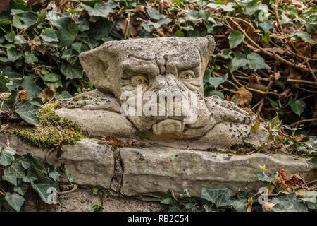 Little goblin Kopf auf einer Steinmauer, wie aus einem Märchen Stockbild