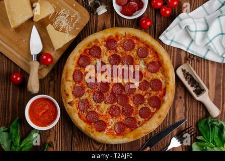 Italienische Pizza auf Holz Tisch mit Zutaten Stockbild