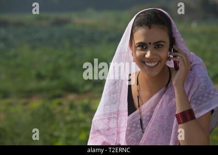 Porträt eines lächelnden Frau, die in einem landwirtschaftlichen Gebiet, die den Kopf von saree Sprechen über Handy abgedeckt. Stockbild