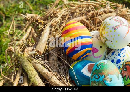Detail bemalte Ostereier mit verschiedenen Formen, Cartoons und helle Farben in einem Vogelnest im Freien an einem sonnigen Tag Stockbild