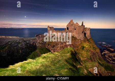 Dunluce Castle gefangen in der Nacht im Mondlicht. Stockbild