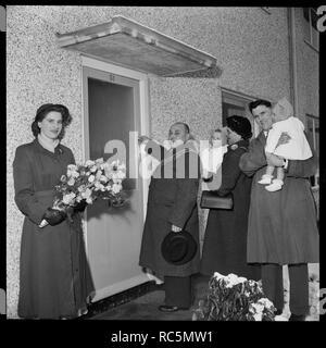 """Haus Eröffnungsfeier, Ramsbury Avenue, Penhill, Swindon, Wiltshire, 1955 Bürgermeister von Swindon Arthur Madge Bennett feierlich Öffnen der vorderen Tür der 3000Th Nachkriegszeit Haus in der Stadt aufgebaut werden, während eine Familie wartet hinter sich. Die original Laing handlist Records das Thema für dieses Bild als """"Öffnung der 3000Th Haus in Swindon. Stockbild"""