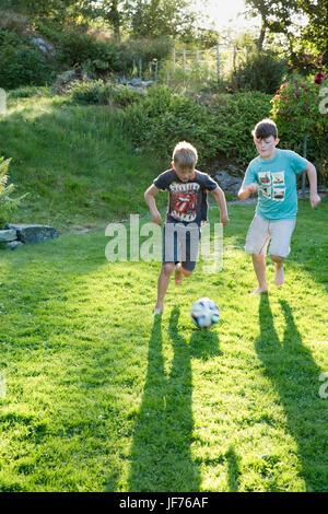 Jungs spielen Fußball im Garten Stockbild