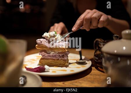 Mittelteil der Frau mit Kuchen sitzen im Restaurant Stockbild