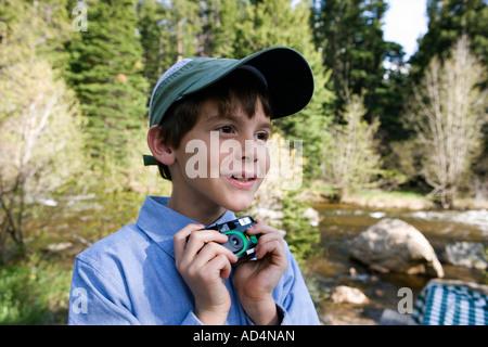 Ein kleiner Junge hält eine Einweg-Kamera an einem Fluss Stockbild