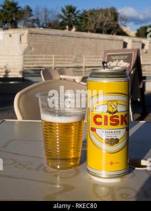 Ein kann der lokalen Lagerbier Marke Cisk und einem Kunststoff Glas in einer Ope-Bar in Malta mit der stadtbefestigung von Mdina im Hintergrund Stockbild