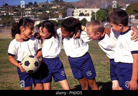 Gruppe junger Kinder stellten sich in einer Reihe mit Arme um einander © Myrleen Pearson... Ferguson Cate Stockbild